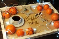 Mandarines, café, decoración y guirnalda en una bandeja de madera con grabado Foto de archivo