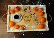 Mandarines, café, decoración y guirnalda en una bandeja de madera con grabado Fotografía de archivo libre de regalías
