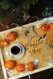 Mandarines, café, decoración y guirnalda en una bandeja de madera con grabado Fotos de archivo libres de regalías