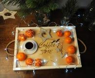 Mandarines, café, decoración y guirnalda en una bandeja de madera con grabado Imagenes de archivo