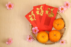 3 mandarines chinoises dans le panier avec les paquets rouges chinois de nouvelle année - série 3 Photo libre de droits