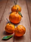 Mandarines con las ramitas y las hojas en un fondo de madera Foto de archivo