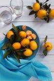 Mandarines d'un plat bleu et des verres de l'eau Photos stock