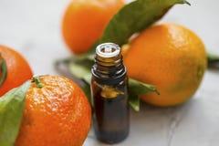 Mandarines de close-up van de etherische oliefles, aromatherapy citrusvruchtenolie met mandarine vruchten stock afbeeldingen