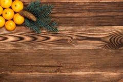 Mandarines de la Navidad y del Año Nuevo al lado de las ramas de árbol de navidad con los conos en un fondo de madera Imagen de archivo libre de regalías