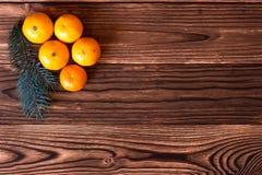 Mandarines de la Navidad y del Año Nuevo al lado de las ramas de árbol de navidad con los conos en un fondo de madera Imagen de archivo