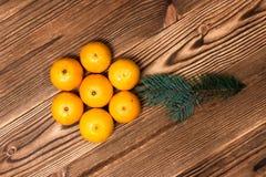 Mandarines de la Navidad y del Año Nuevo al lado de las ramas de árbol de navidad con los conos en un fondo de madera Imagenes de archivo