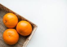 Mandarines de un par en cesta de mimbre en una opinión superior del fondo blanco Imagen de archivo