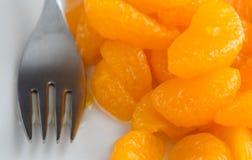 Mandarines en boîte d'un plat avec la fourchette Image stock
