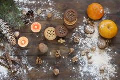 Mandarines et biscuits en décor de Noël avec l'arbre, les écrous et les pommes de Noël sur le fond en bois foncé Photographie stock