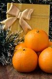 Mandarines et cadeau oranges d'or photos stock