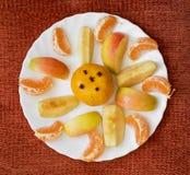 Mandarines et pommes coupées en tranches d'un plat blanc Photos libres de droits