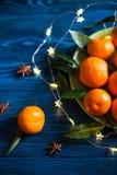 Mandarines fraîches avec des feuilles sur la table en bois rustique de marine avec l'anis de guirlande et d'étoile photographie stock