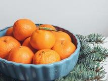 Mandarines fragantes que mienten en la tabla cerca del árbol de navidad Foto de archivo libre de regalías
