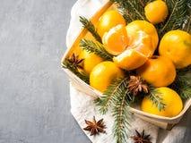 Mandarines frescos en una cesta de madera con las ramas de árbol de abeto, canela del anís de estrella en espacio gris de la copi Foto de archivo libre de regalías