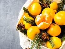 Mandarines frescos en una cesta de madera con las ramas de árbol de abeto, canela del anís de estrella en espacio gris de la copi Fotos de archivo libres de regalías