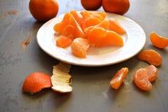 Mandarines, gepelde mandarijn en mandarijnplakken op een houten lijst Stock Foto