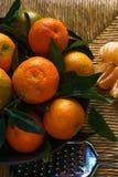 Mandarines mûres avec des feuilles sur la table rustique avec le tissu photos stock
