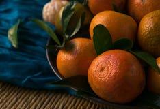 Mandarines mûres avec des feuilles sur la table rustique avec le tissu image stock