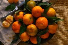 Mandarines mûres avec des feuilles sur la table rustique avec le tissu images stock