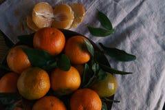 Mandarines mûres avec des feuilles sur la table rustique avec le tissu photographie stock