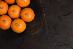 Mandarines mûres fraîches sur le conseil en bois sur le fond noir - fin vers le haut de la photographie des agrumes crus entiers  photos libres de droits
