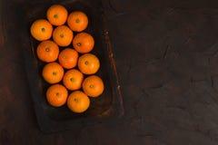Mandarines mûres fraîches sur le conseil en bois sur le fond noir - fin vers le haut de la photographie des agrumes crus entiers  images libres de droits