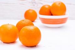 Mandarines maduros en una tabla y en un cuenco Imagen de archivo