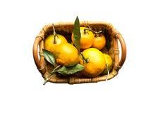 Mandarines oranges fraîches avec des feuilles dans le panier de paille d'isolement sur le blanc Photographie stock
