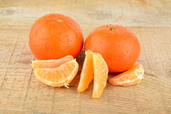 Mandarines with pieces isolated on wooden table Stock Photography