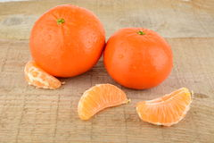 Mandarines with pieces isolated on wooden table Royalty Free Stock Image