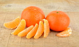 Mandarines with pieces isolated on wooden table Stock Images