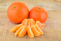 Mandarines with pieces  on wooden table Stock Photo