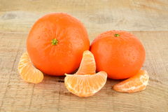 Mandarines with pieces  on wooden table Royalty Free Stock Photo