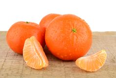 Mandarines with pieces  on wooden table Royalty Free Stock Photos