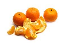 Mandarines y rebanadas maduros con la cáscara aislada en el primer blanco del fondo Fotografía de archivo libre de regalías