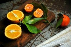 Mandarines y zumo de naranja en un fondo del vintage Fotografía de archivo