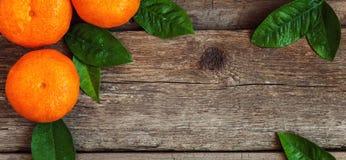 Mandarini con le foglie su fondo di legno Fotografia Stock