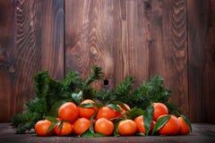 Mandarini con le foglie su superficie di legno Fotografia Stock