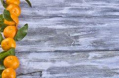 Mandarini con le foglie su un fondo di legno fotografie stock