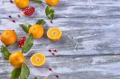 Mandarini con le foglie su un fondo di legno fotografia stock