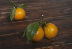 Mandarini con le foglie verdi su un fondo di legno, natura morta immagine stock libera da diritti