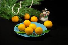 Mandarini di Natale su un piatto blu Immagini Stock