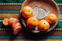 Mandarini e carota su un piatto di terra su una tovaglia luminosa Immagini Stock