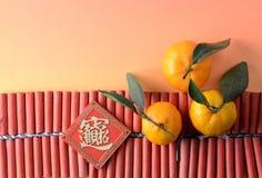 Mandarini ed ornamento promettente sui petardi Fotografie Stock Libere da Diritti