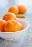 Mandarini in piatto bianco sulla tavola di legno Immagini Stock