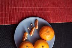 Mandarini in piatto su fondo nero e rosso immagini stock libere da diritti