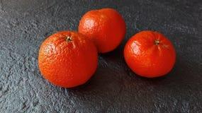 Mandarini su un sollievo scuro del calcestruzzo del fondo Immagine Stock