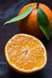 Mandarino aperto tagliando su fondo di legno di mogano fotografia stock