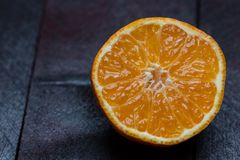 Mandarino aperto tagliando su fondo di legno di mogano immagine stock libera da diritti